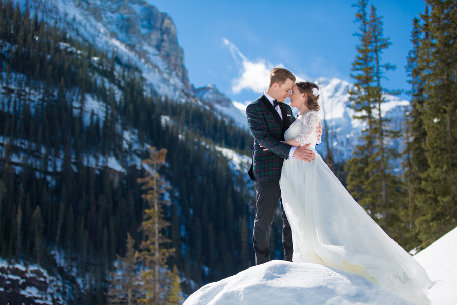 bride and groom standing at the foot of a mountain