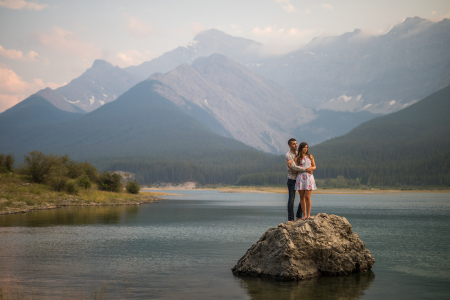 couple standing on a rock, canmore engagement session, engagement session in the water