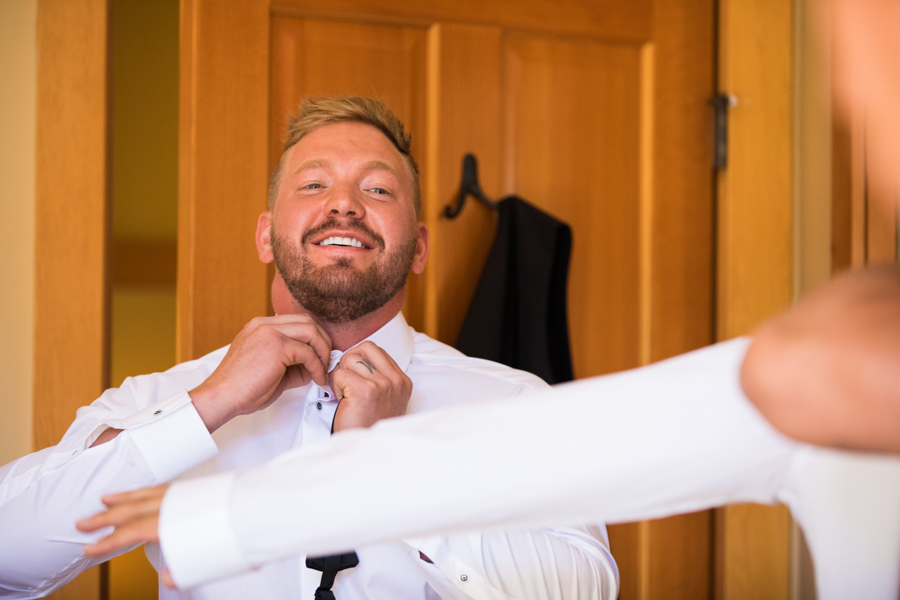 groom getting ready, in panorama bc, groom doing up his shirt