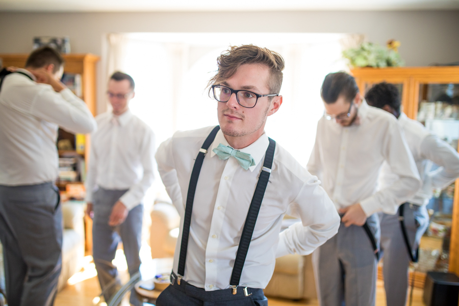 groom wearing suspenders, groom getting ready
