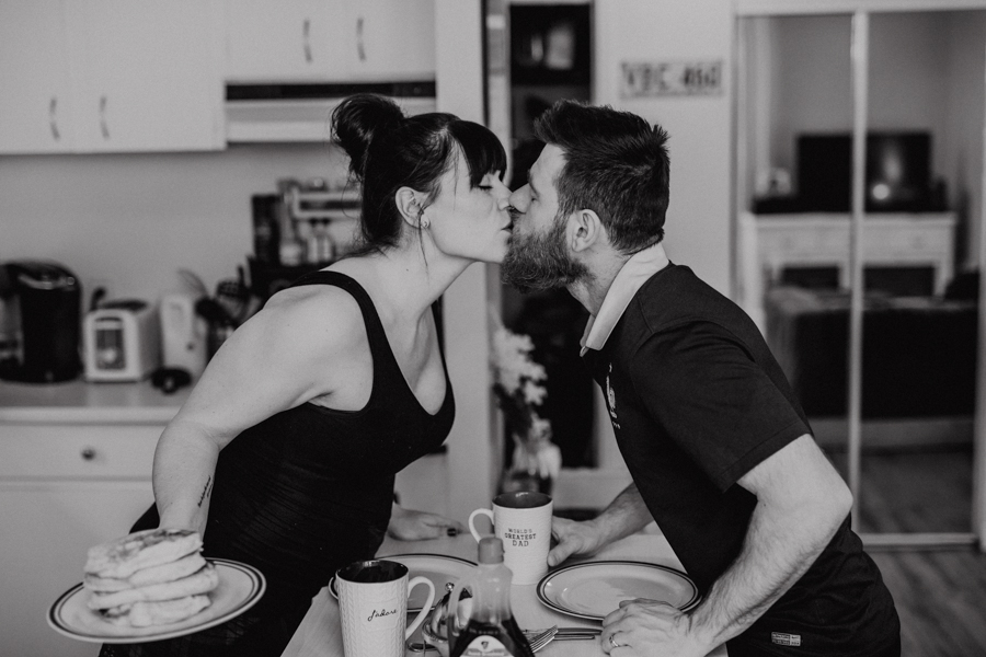 kissing in the kitchen with maternity photos