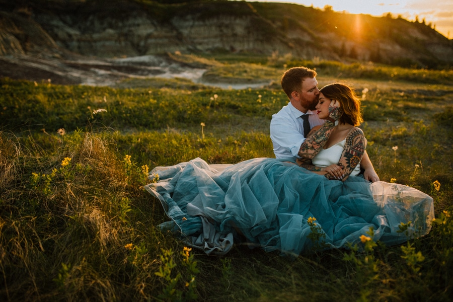 day after session bride and groom cuddle in Drumheller alberta in funky stylish clothing.