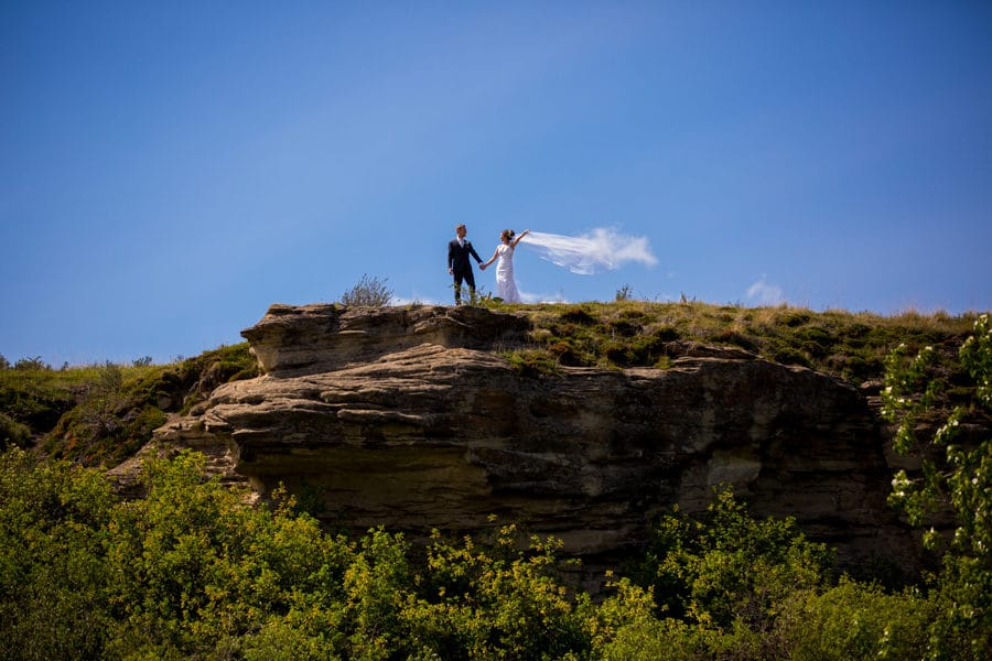 a bride and groom taking a walk at the cochrane ranch house field