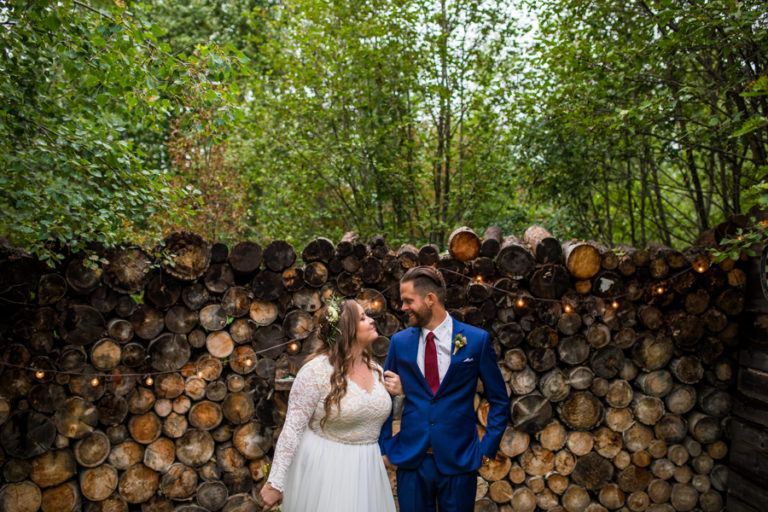 woodland and wildflower wedding venue with the bride and groom in front of the wood pile
