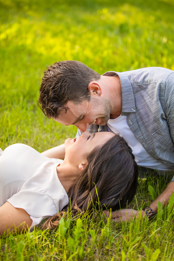 he is kissing her on the green grass of their ranch