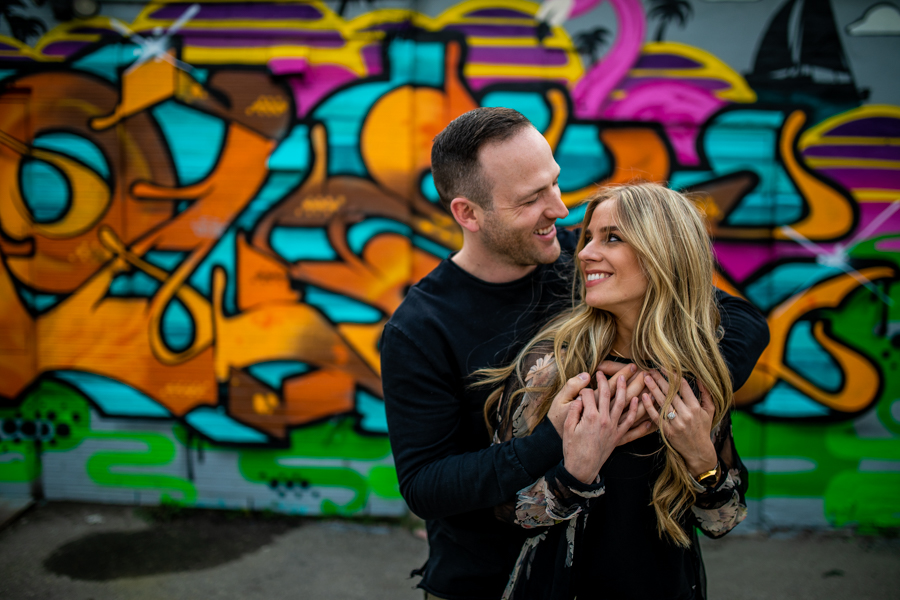 couple getting a picture taken infant of graffiti