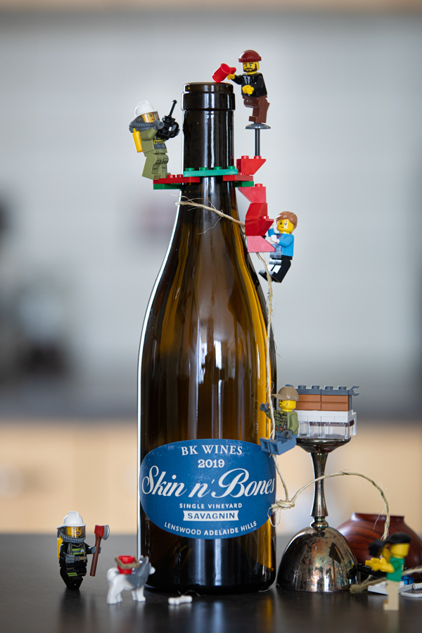 lego men climbing a wine bottle