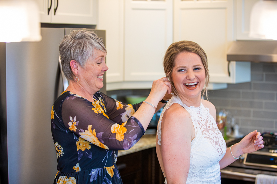 mom helping bride with her hair