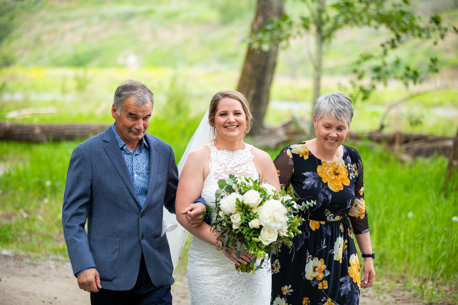 bride walking with parents to her fish creek park elopement