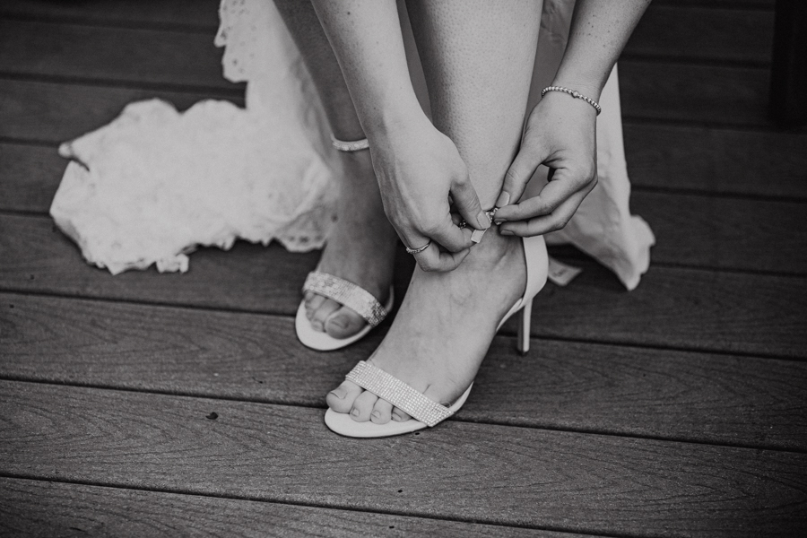 Bride doing up her shoes for a back yard wedding