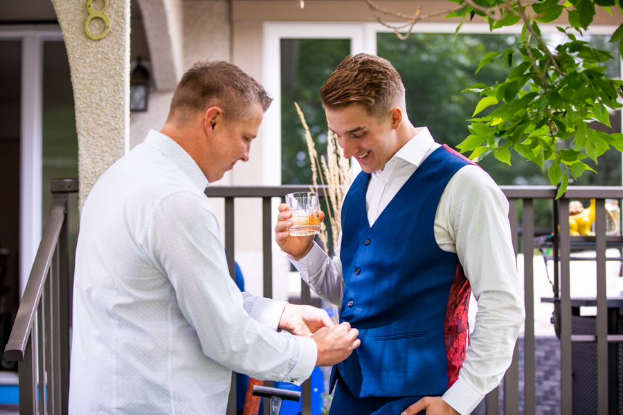 groom getting his vest buttoned up