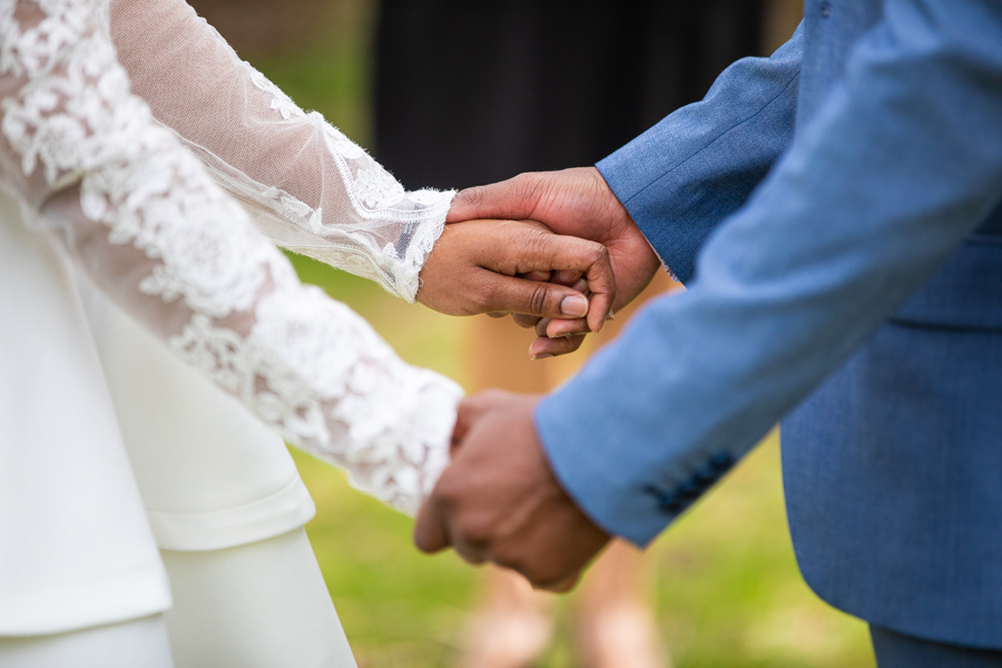 couple hiding hands ready to elope in Lindsay Park