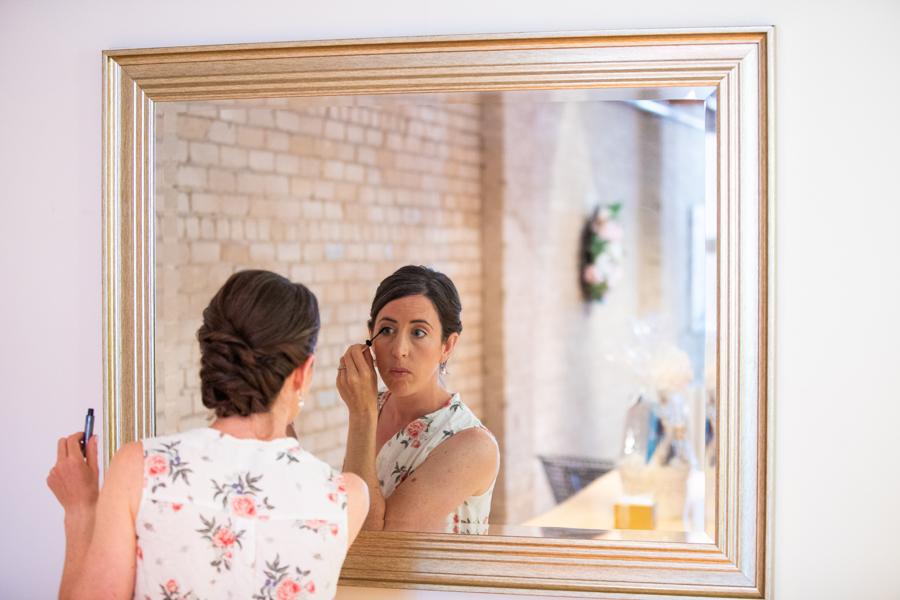 Bride putting on make up in edmonton elopement