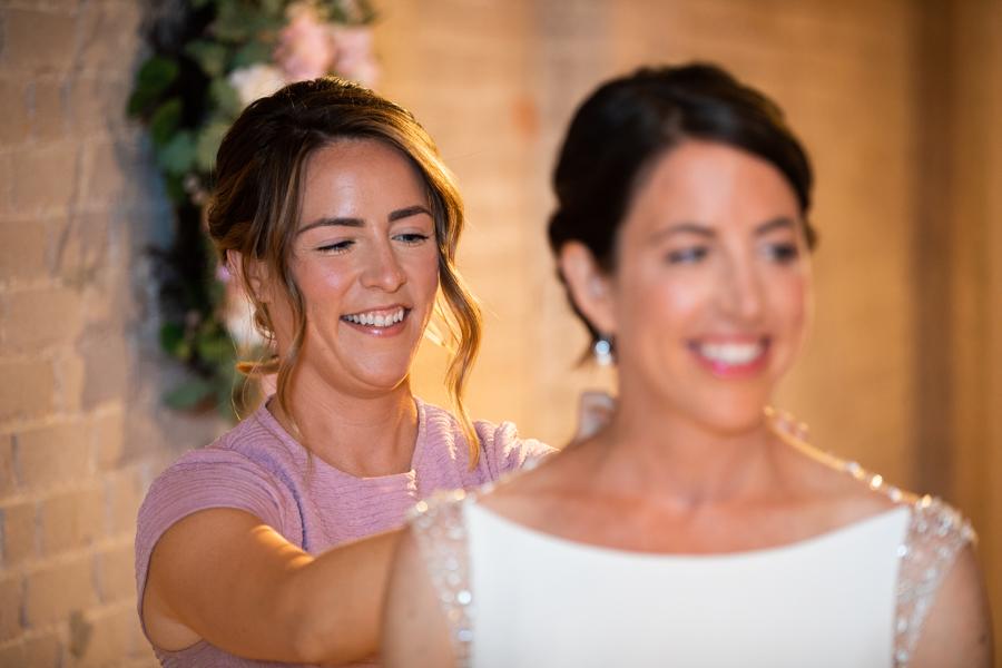 sister helping bride with dress in rooftop wedding in edmonton