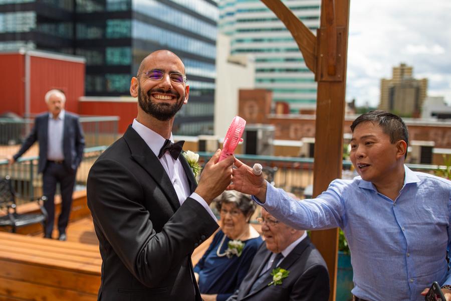 groom using a fan on rooftop elopement in edmonton