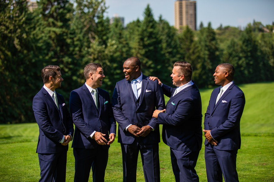 groom and groomsmen standing on the golf course