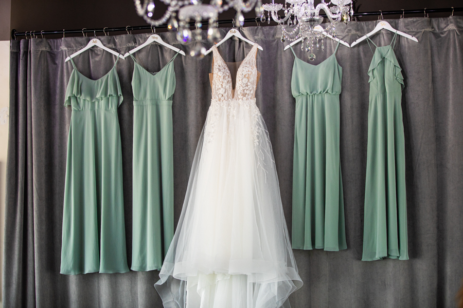 brides maids drees and bridal gown hanging in make up shop