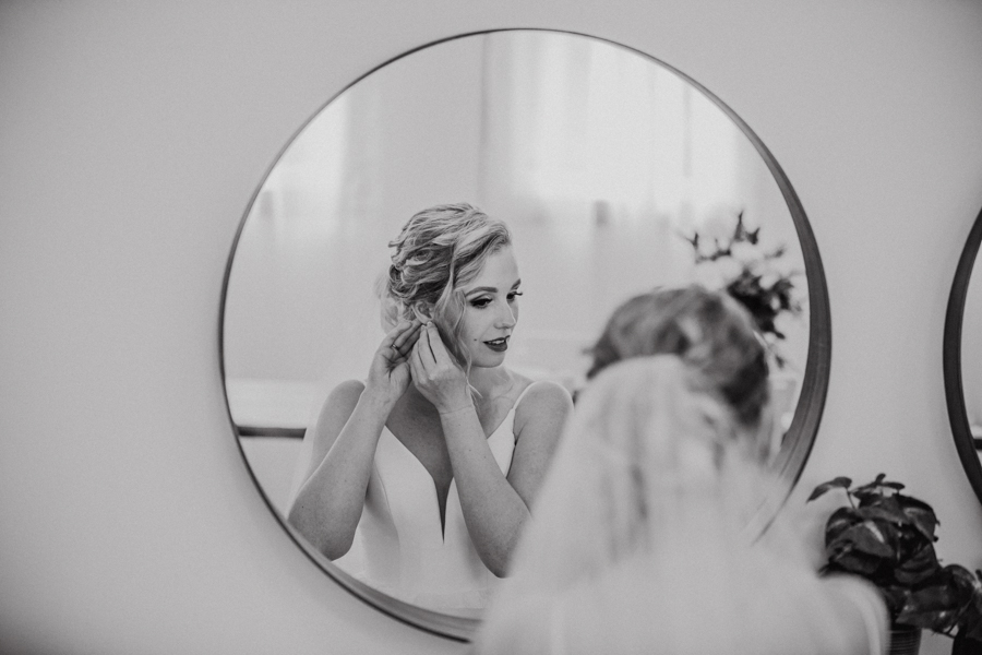 bride in mirror getting ready at the school house on pine and pond wedding venue