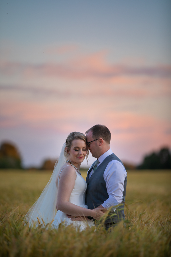 amazing sunset in a wheat field with couple at pine and pond
