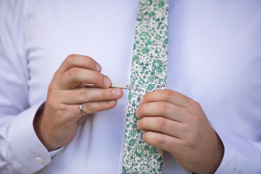 groom putting on tie clip