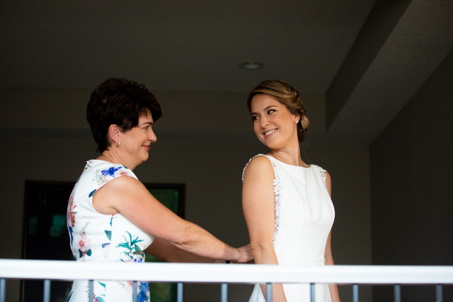 mom helping bride wither dress