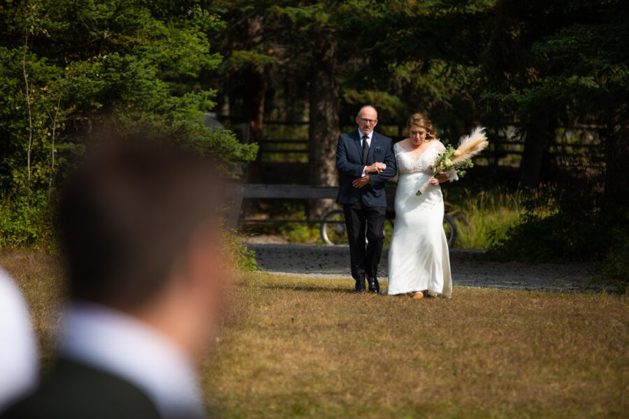 bride and dad walking down the aisle at Canmore Ranch wedding venue
