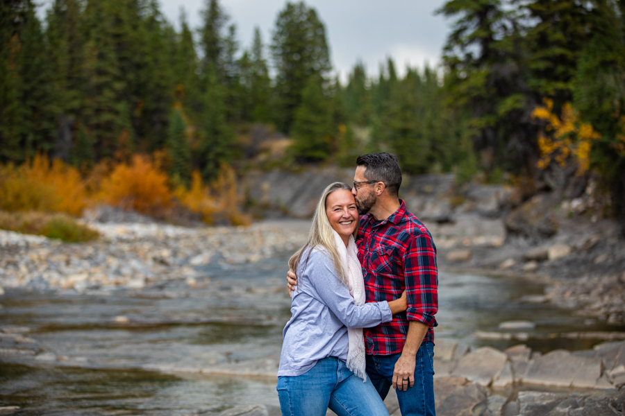 couple kissing along a river bank