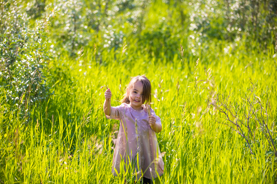 little girl running through long grass in fish creek park