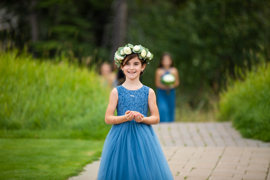 Flower girl coming down the aisle at silvertip canmore elopement
