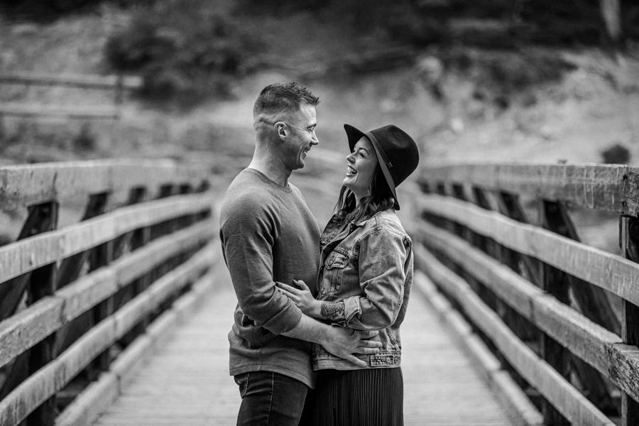 couples cuddling on a bridge