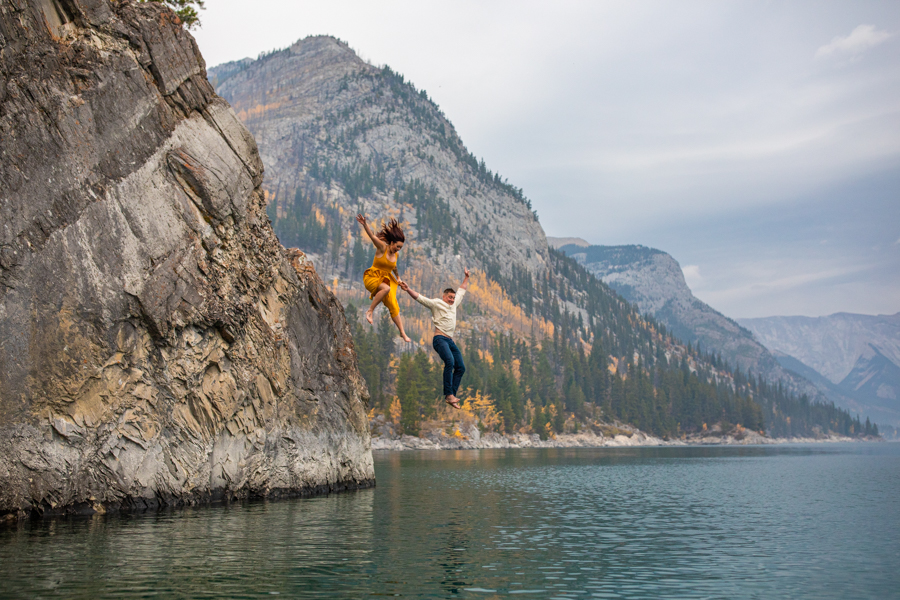 Lake minnewanka sunrise engagement, couple in the water at lake minnewanka, lake minnewanka cliff jumping couple