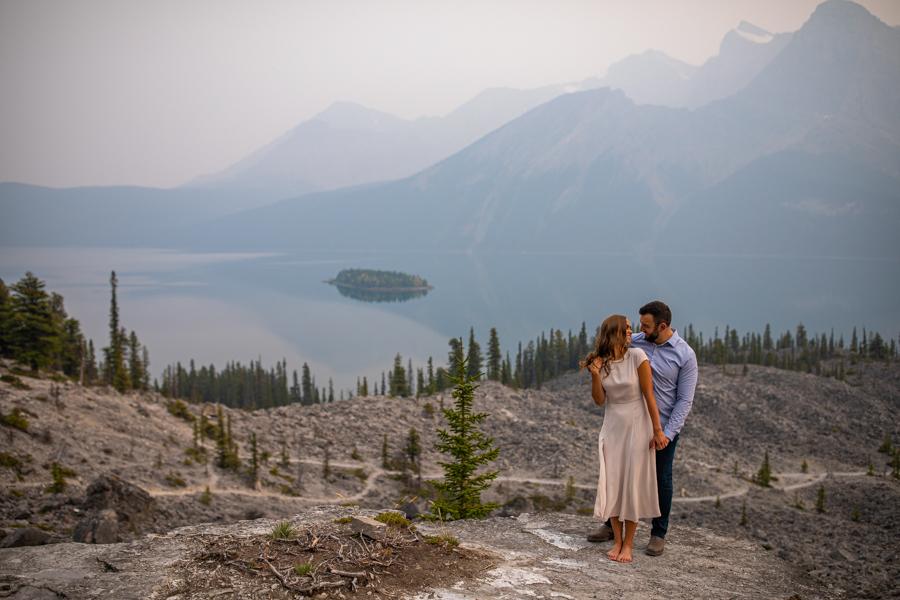 couple cuddling by a lake
